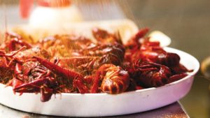 feature-crawfish-getting-dusted-seasoning